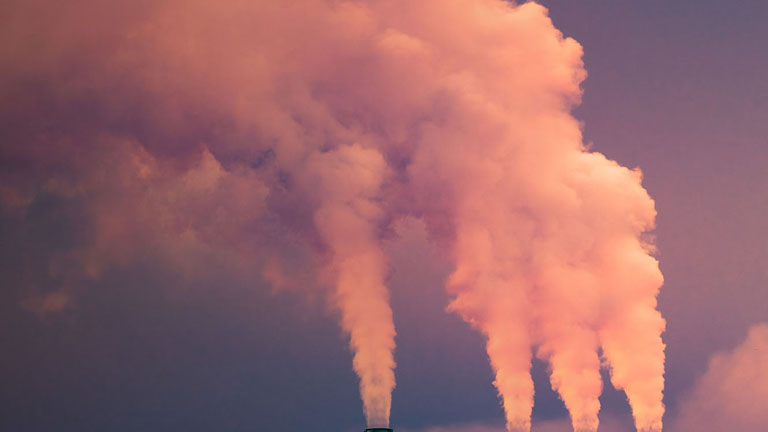Smoke and steam rising into the air from power plant stacks; dark clouds background; concept for environmental pollution and climate change